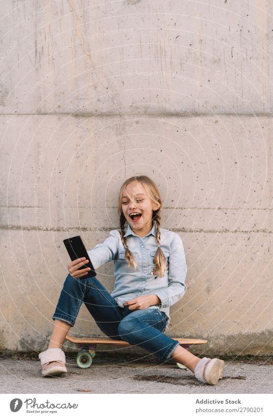 Kind mit Handy und Skate Bildschirm Halt Technik & Technologie Außenaufnahme Spielen digital Tablet Computer Freizeit & Hobby Gerät benutzend Freude lässig