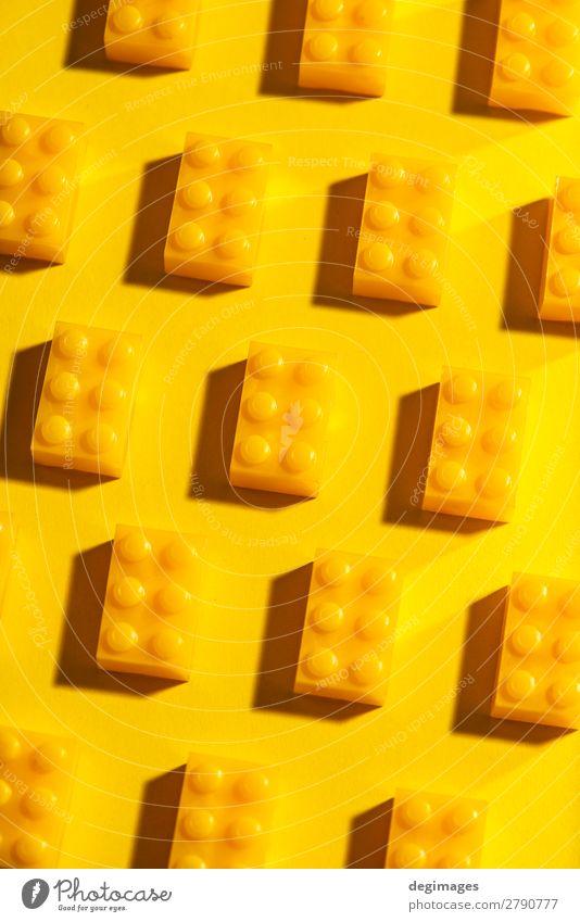 Gelbe, einfarbige geometrische Kunststoffwürfel. Bauspielzeug Design Spielen Kind Kindheit Spielzeug Backstein bauen gelb Farbe Blöcke Hintergrund Reihen