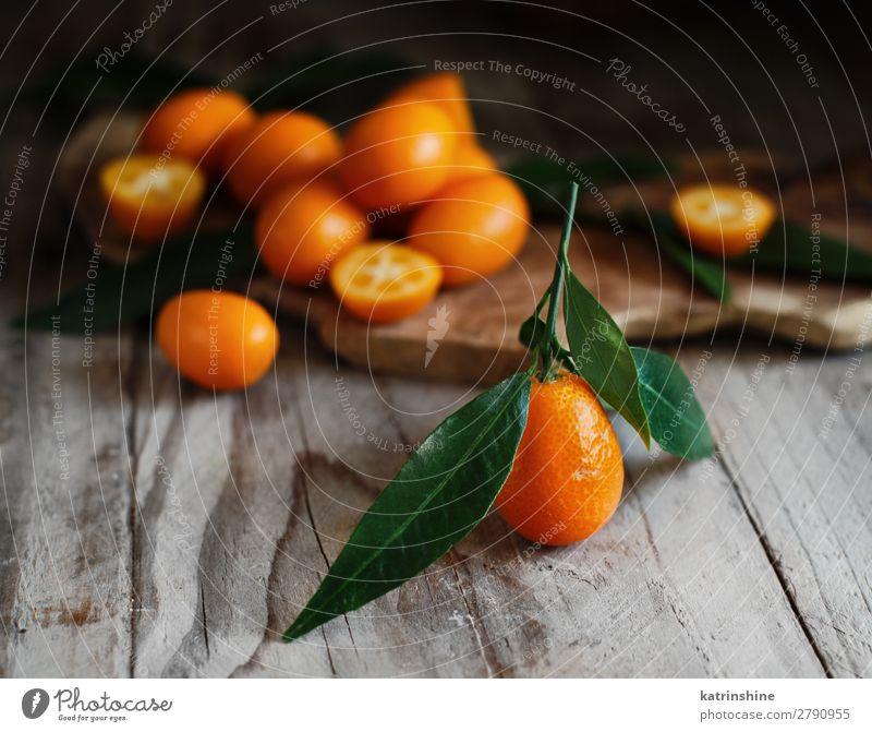 Kumquat-Früchte auf Holzuntergrund Frucht Dessert Ernährung Vegetarische Ernährung Diät exotisch Menschengruppe Blatt frisch natürlich saftig gelb grau Farbe