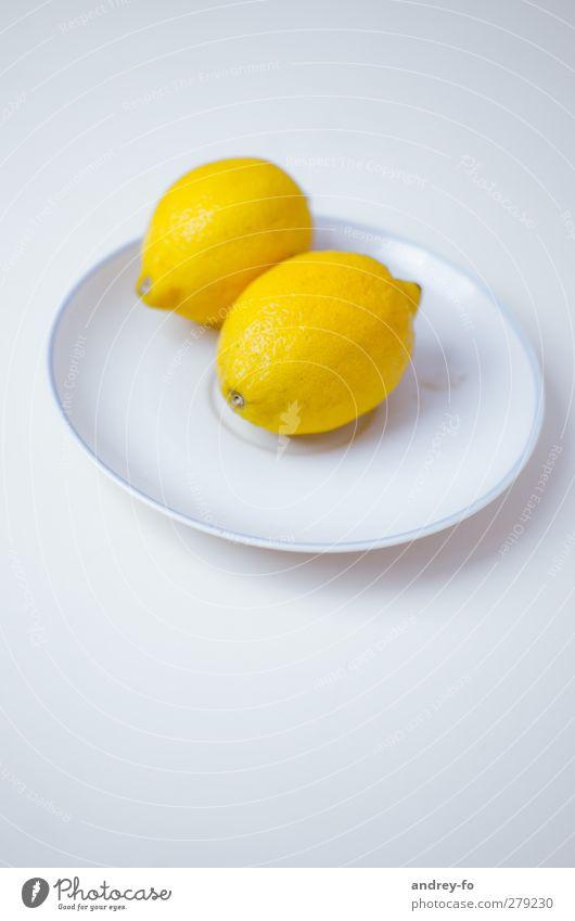 Zwei Zitronen. Leben sauer gelb Zitrusfrüchte Teller liegen Foodfotografie Essen minimalistisch lecker frisch Bioprodukte 2 Tellerrand hell rund