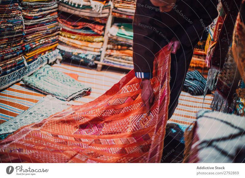 Verkäufer zeigt Teppich auf dem Markt zeigen Geschenk rot Wahl pflücken Osten Basar Tradition kaufen Lager Tourismus mehrfarbig Chechaouen Marokko Sale