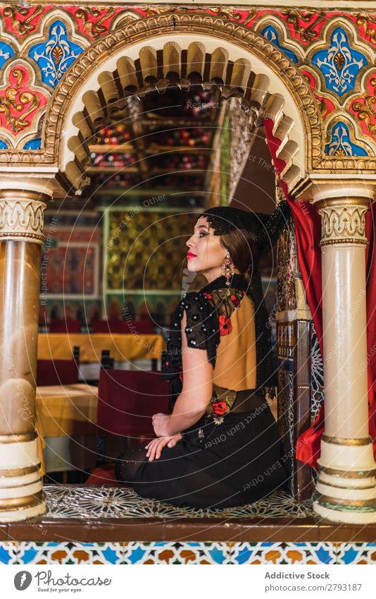 Charmante Frau in Kleidern im Restaurant Reichtum Tisch Café Mosaik charmant Raum Stuhl Design Dame Leidenschaft sitzen schön Möbel Schminke Innenarchitektur