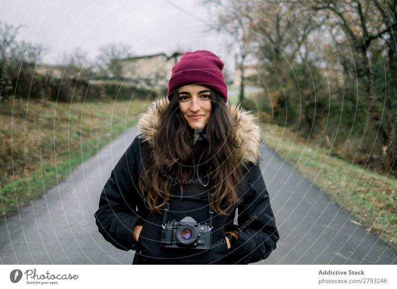 Lächelnde Frau im Mantel mit Kamera Fotokamera Landschaft Orduna Spanien Dame Hut Hand Tasche heiter anhaben Winter attraktiv Jugendliche Straße