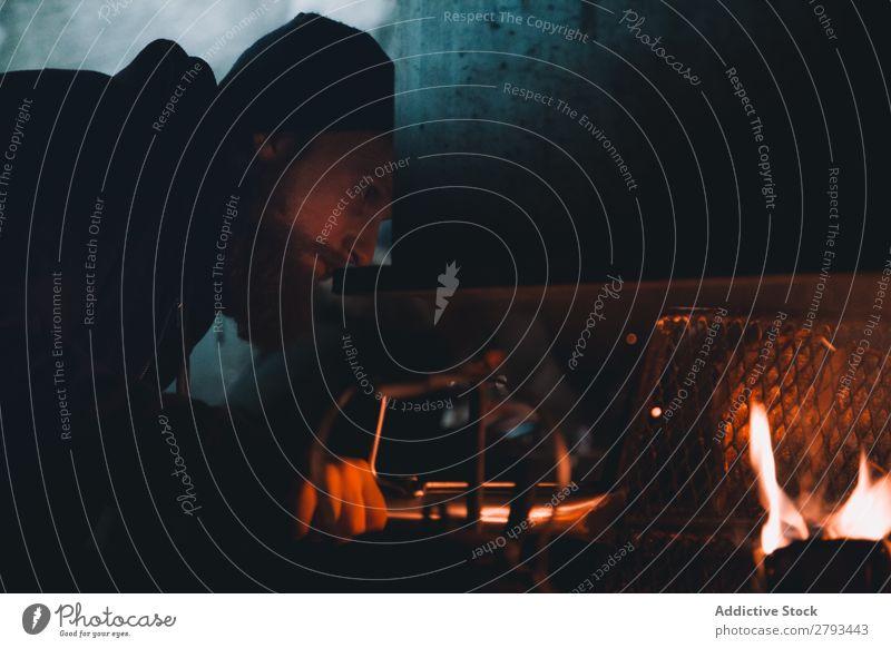 Bartiger Mann in der Nähe des Verbrennungsofens Schmelzofen Feuer Arktis heizen heiß Metall Flamme Eisen bärtig Gerät hell Wärme Norden polar schäbig Energie