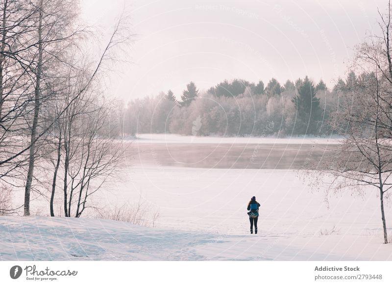 Anonyme Frau, die in schneebedeckter Landschaft am Fluss steht. Winter gefroren Schnee Arktis kalt