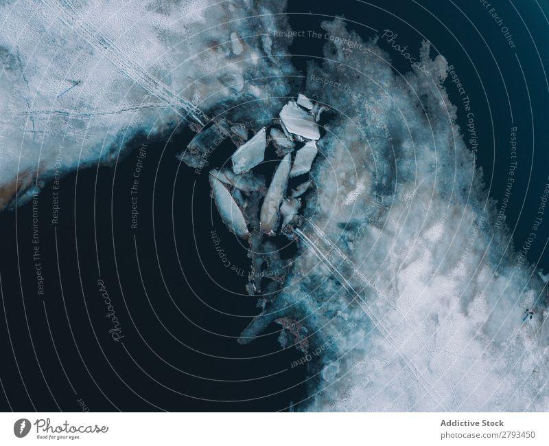Eisplatten in der Nähe von schneebedeckten Ufern Platten Wasser Arktis Küste Schnee kalt kaputt Oberfläche Meer Frost Schaden Coolness dunkel Menschenleer