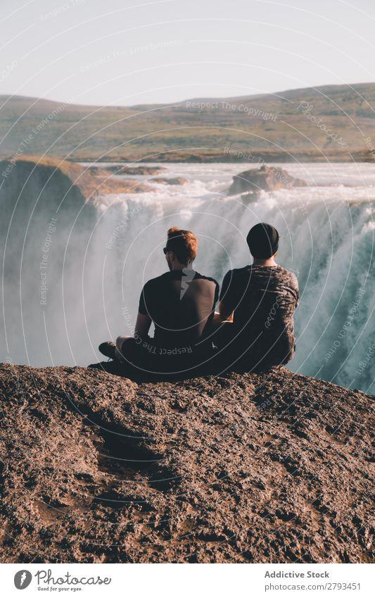 Anonyme Männer beim Betrachten des Wasserfalls Mann Klippe Aussicht Natur Landschaft Arktis