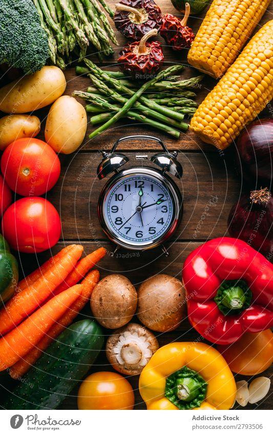 Gemüse, das um den Wecker herum liegt. Zeit Tisch Diät Entwurf Lebensmittel Gesundheit Ernährung organisch Vegane Ernährung Kulisse sortiert Verschiedenheit
