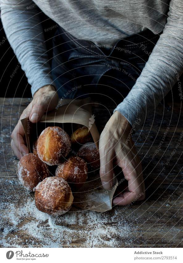Person in der Nähe von gebackenen Kuchen auf dem Tisch Mensch Brotlaib Zucker gepulvert Lebensmittel Holz Backwaren Kulisse Mahlzeit Bäckerei süß Dessert