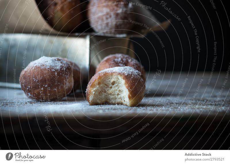 Gebackene Kuchen auf dem Tisch gebissen Kulisse Brotlaib Zucker gepulvert Dunkelheit Lebensmittel Backwaren Mahlzeit Bäckerei süß Dessert Pasteten Ernährung