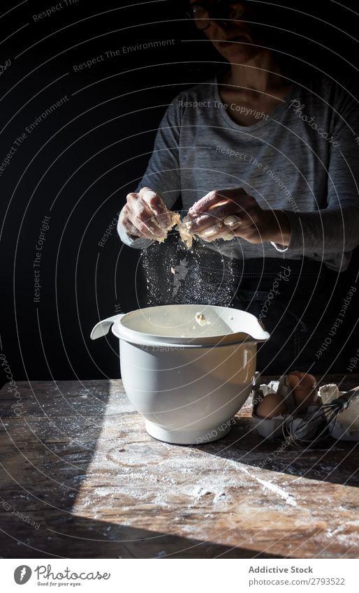 Person, die das Ei in der Schüssel auf dem Tisch knackt. Schalen & Schüsseln kochen & garen Mehl Rissbildung Holz Mahlzeit Handwerk brechen geschmackvoll Mensch