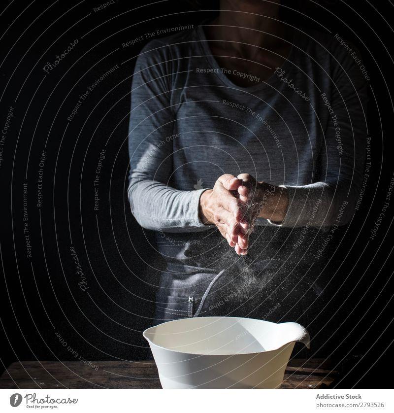 Frau klatscht mit den Händen in Mehl in der Nähe der Schüssel und der Eierpackung auf dem Tisch. Hand Schalen & Schüsseln Rudel Applaus Rührbesen Holz Mahlzeit