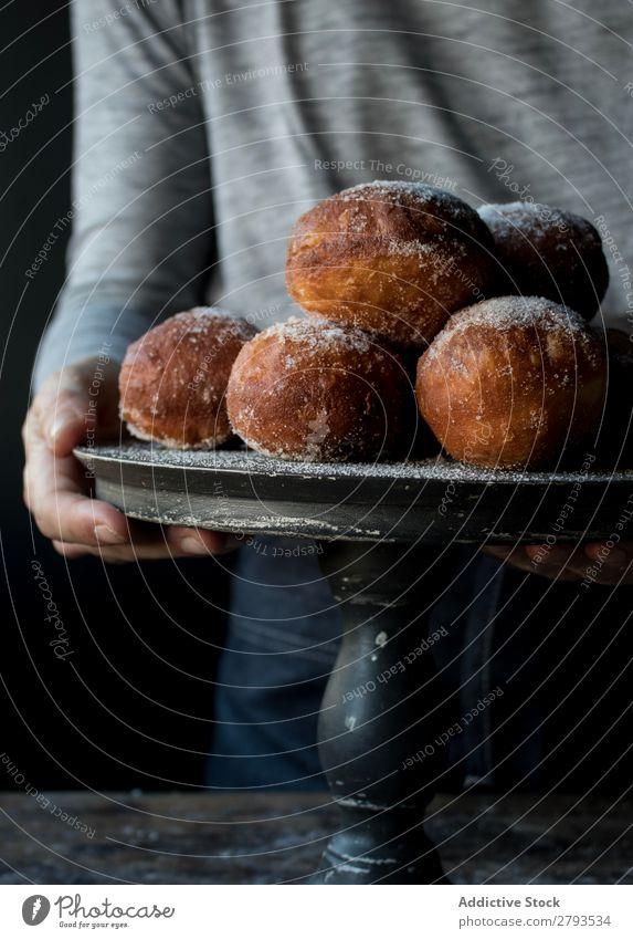 Person in der Nähe von gebackenen Kuchen auf dem Ständer auf dem Tisch Mensch Tablett Brotlaib Zucker gepulvert Dunkelheit Lebensmittel Holz Backwaren Kulisse