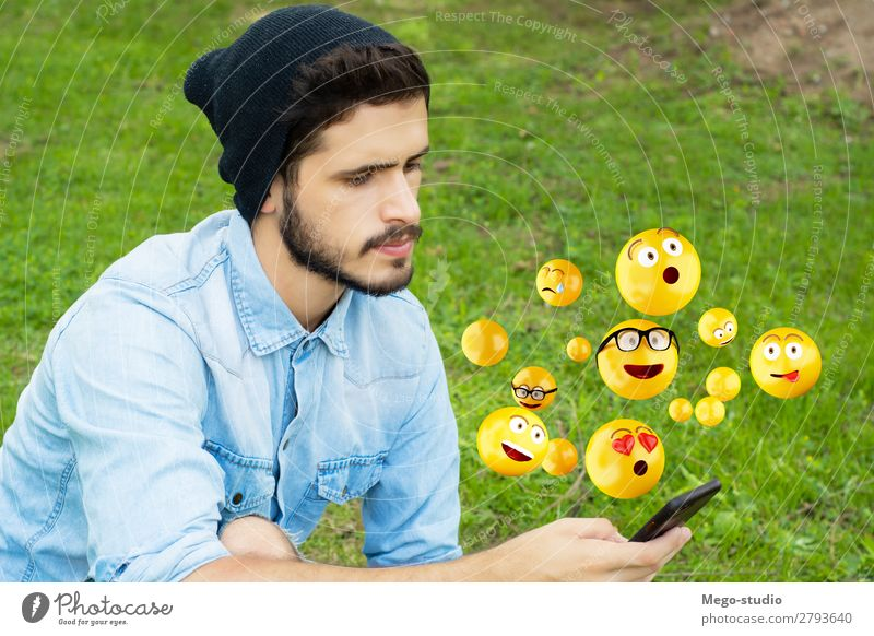 Junger Mann, der mit dem Smartphone Emojis sendet. Lifestyle Glück Gesicht Telefon PDA Bildschirm Technik & Technologie Internet Mensch Erwachsene Hand lustig