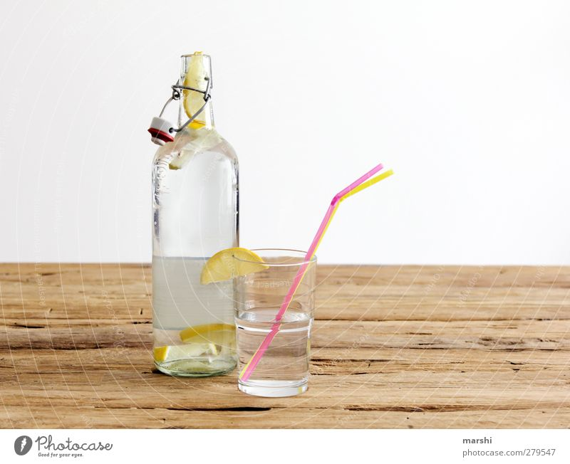 Zitronenlimonade Getränk trinken Erfrischungsgetränk Limonade Flasche Glas gelb Frucht fruchtig Halm Durstlöscher Wasser Holztisch Farbfoto Innenaufnahme