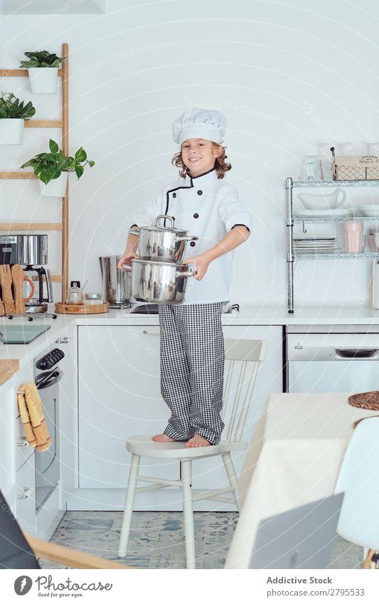 Lächelnder Junge mit Kochmütze hält Töpfe auf Stuhl in der Küche. Topf Küchenchef Kind Hut kochen & garen modern heimwärts Glück Licht vorbereitend Fröhlichkeit