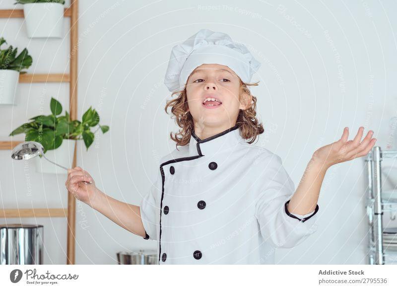 Junge mit Kochmütze, der die Schöpfkelle hält und den Daumen in der Küche zeigt. Schöpflöffel Daumen hoch Küchenchef Kind Hut Coolness gestikulieren