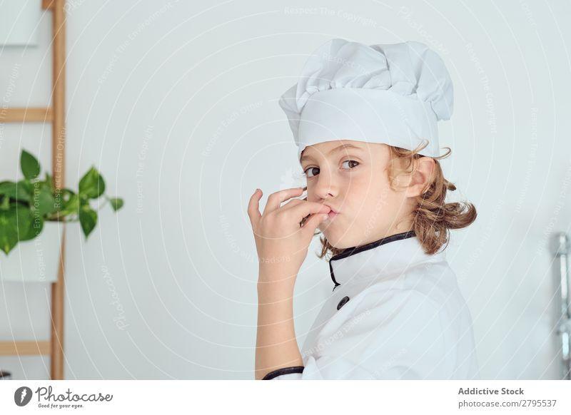 Junge mit Kochmütze mit leckerer Geste in der Küche Küchenchef Kind Hut Coolness gestikulieren kochen & garen modern heimwärts Feinschmecker zeigen Licht