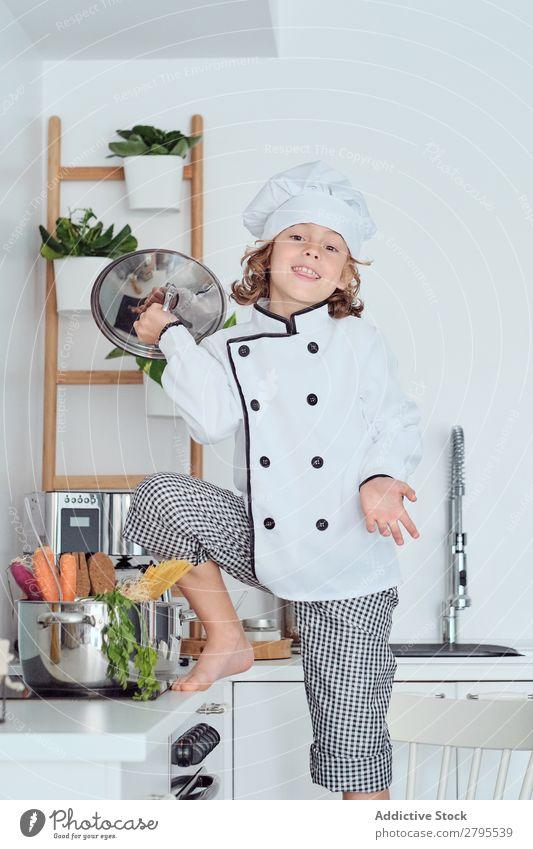 Junge mit Kochmütze mit Deckel neben dem Topf auf Stuhl in der Küche überdeckt Küchenchef Kind Gemüse Hut kochen & garen modern lustig heimwärts Licht