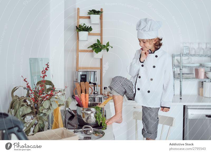 Junge mit Kochmütze mit erhobener Hand in der Nähe des Topfes auf Stuhl in der Küche. erhöht Küchenchef Kind Gemüse Hut kochen & garen modern lustig heimwärts