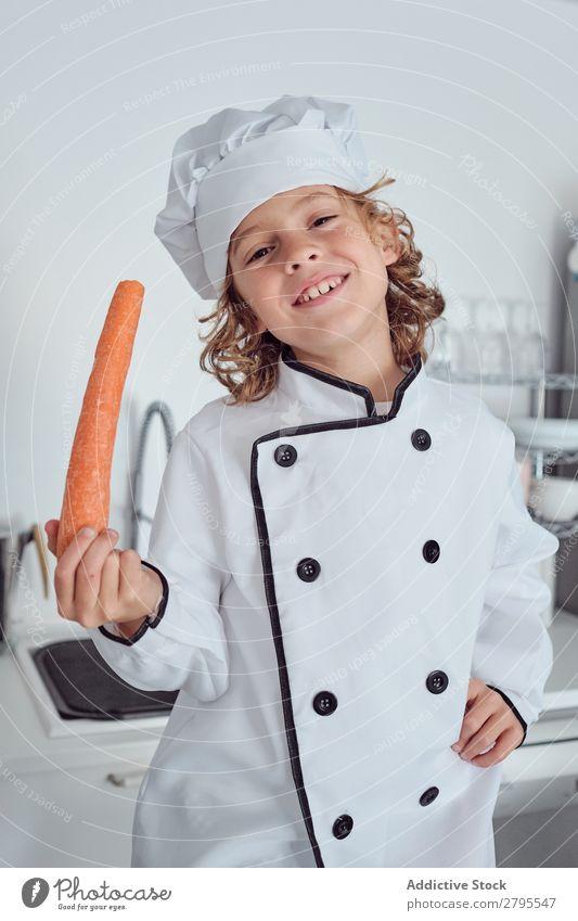 Junge mit Kochmütze mit Karotte in der Küche Möhre Küchenchef Kind Gemüse Hut frisch zeigen Hand Hüfte kochen & garen modern lustig heimwärts Licht vorbereitend