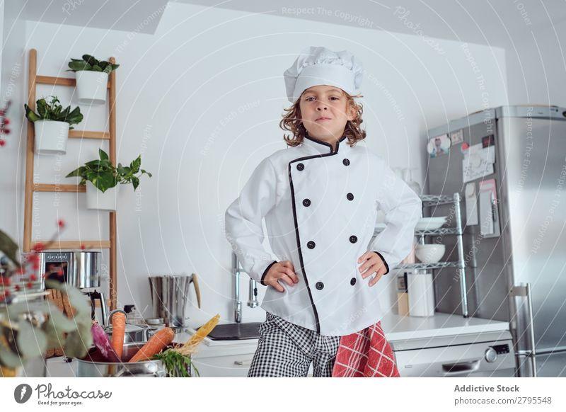 Junge mit Kochmütze in der Küche Möhre Küchenchef Kind Gemüse Hut frisch zeigen Hand Hüfte kochen & garen modern lustig heimwärts Licht vorbereitend
