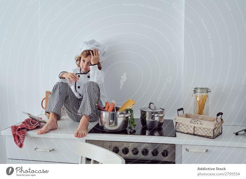 Junge mit Kochmütze neben Töpfen auf der Elektrofritteuse in der Küche sitzend Topf Küchenchef Kind Gemüse Hut Herd & Backofen kochen & garen modern lustig