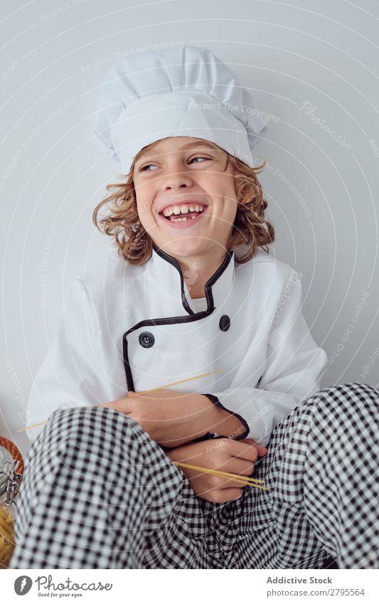 Junge sitzt in der Nähe von Töpfen auf der Elektrofritteuse in der Küche. Koch Topf Küchenchef Kind Gemüse Hut Herd & Backofen kochen & garen modern lustig