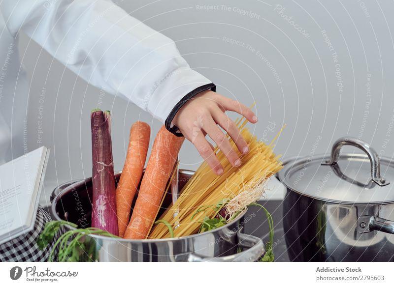 Junge in der Nähe des Topfes mit Gemüse und Nudeln auf der Elektrofritteuse in der Küche Koch Spätzle Küchenchef Kind Hand Herd & Backofen kochen & garen Putten