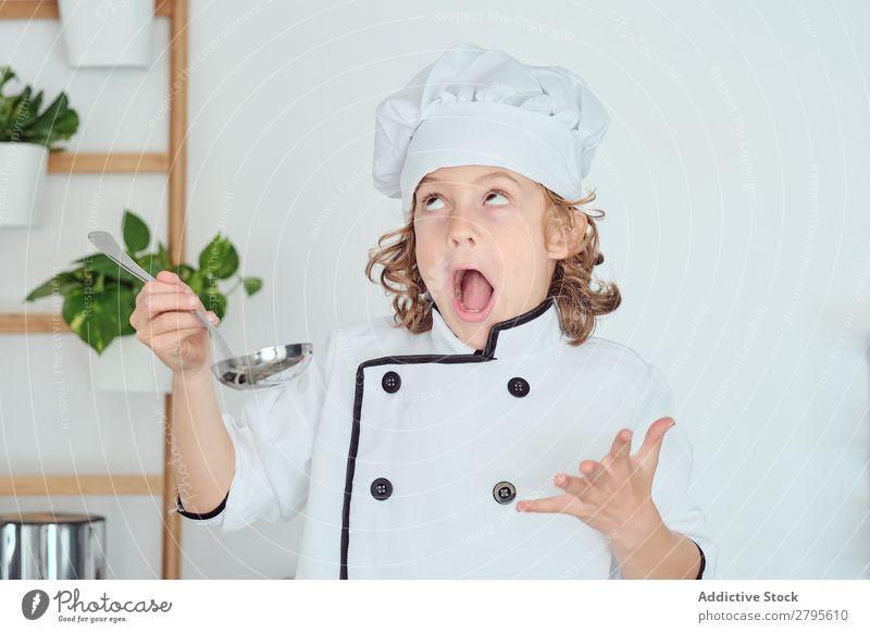 Junge mit Kochmütze hält Schöpfkelle in der Nähe des Mundes in der Küche. Schöpflöffel Küchenchef Kind Topf Verkostung Lebensmittel Hut kochen & garen Metall