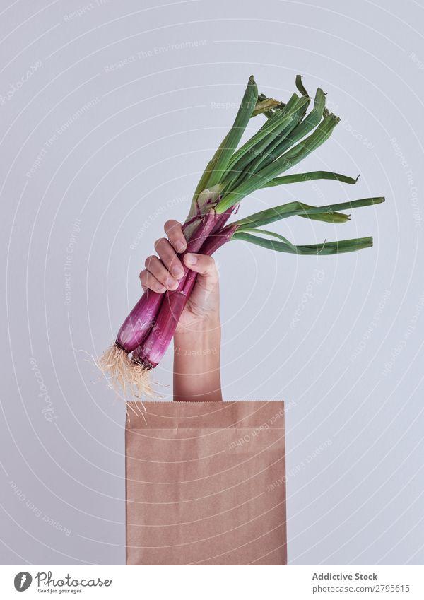 Personenhand aus der Packung ausgestreckt und hält roten Lauch. Mensch Hand Paket sich[Akk] gemeldet Gemüse Lebensmittel Tasche Handwerk Papier Entwurf frisch
