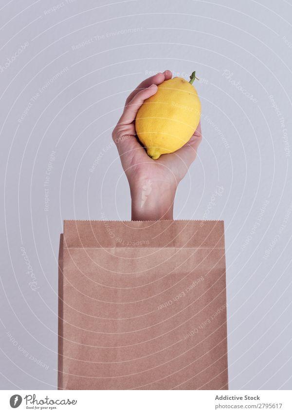 Personenhand aus der Packung ausgestreckt und mit Zitrone gehalten Mensch Hand Möhre Paket sich[Akk] gemeldet Gemüse Lebensmittel Tasche Handwerk Papier Entwurf