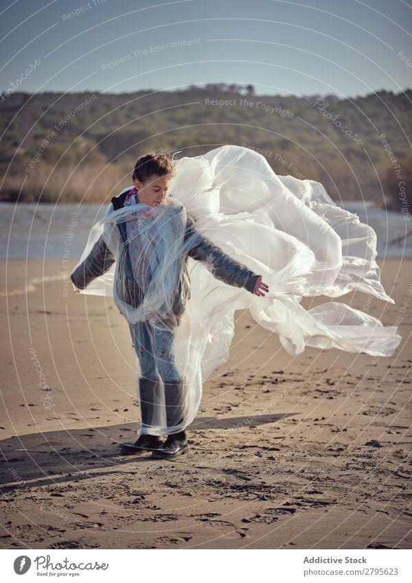 Mädchen in Plastik verstrickt an der Flussküste Kunststoff Textil winkend Küste Seite Wind Sand Wasser Berge u. Gebirge Landschaft Strand Hilfsbereitschaft weiß