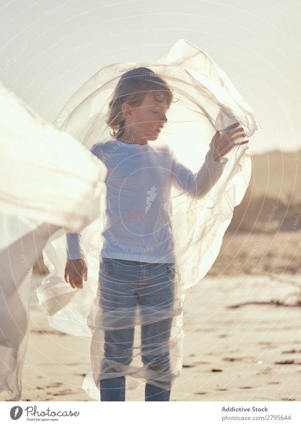 Kind in Plastik verstrickt an der Flussküste Junge Kunststoff Textil winkend Küste Seite Wind Sand Wasser Berge u. Gebirge Landschaft Strand Hilfsbereitschaft