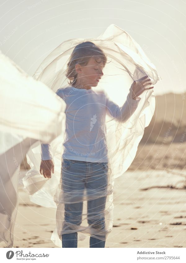 Kind in Plastik verstrickt an der Flussküste Junge Kunststoff Küste Seite Wind