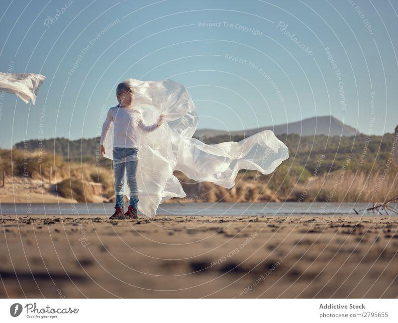 Mädchen in Plastik verstrickt an der Flussküste Kunststoff Küste Seite Wind Sand