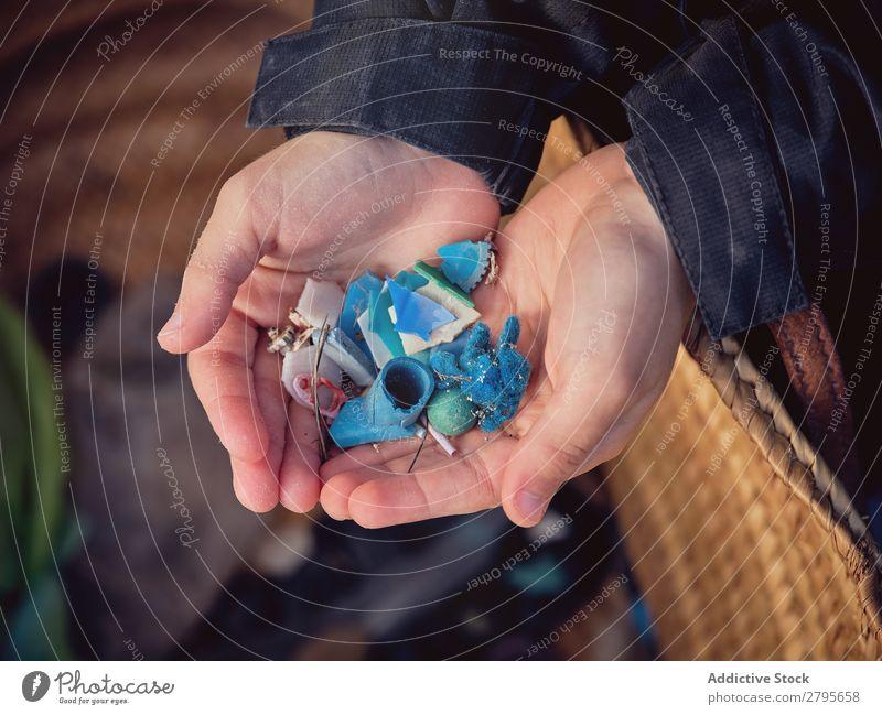Junge mit Müllhaufen in den Händen in der Nähe des Korbes Müllbehälter Haufen Hand Jugendliche Anhäufung Container Boden