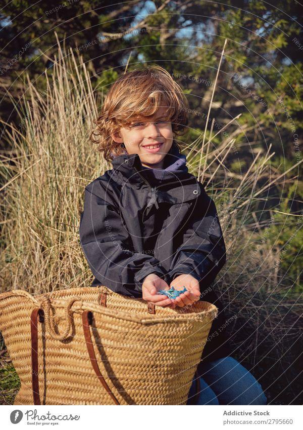 Junge mit Müllhaufen in den Händen in der Nähe des Korbes Müllbehälter Boden Kind Park Container Umwelt Kunststoff
