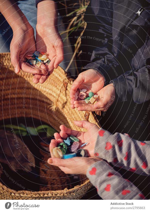 Person und Kinder mit Müllhaufen in den Händen in der Nähe des Korbes Müllbehälter Haufen Hand Mensch Anhäufung Container Kunststoff Aufräumen Jugendliche