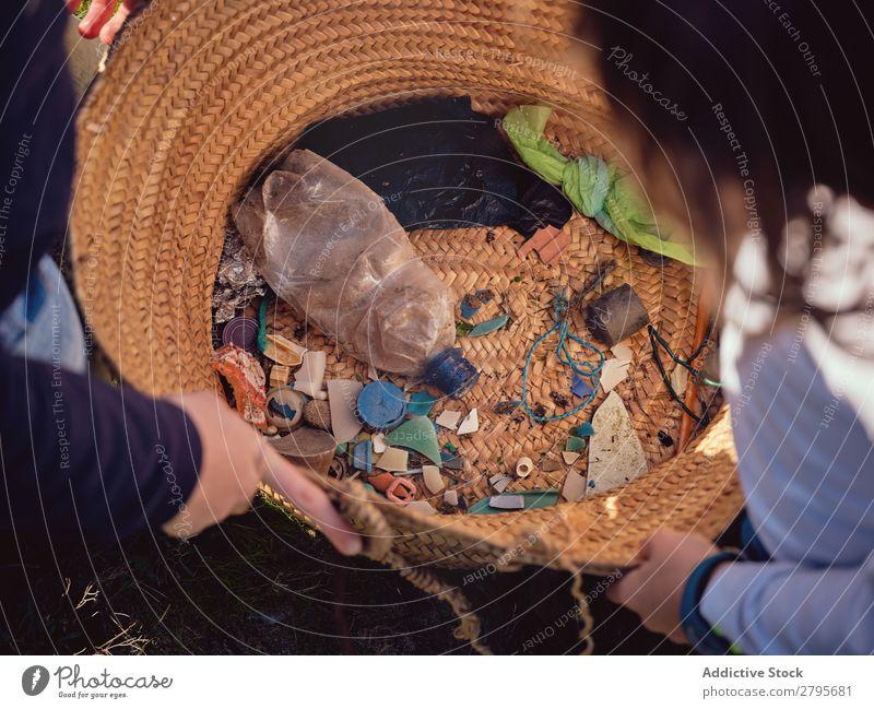 Person und Kinder mit Müllhaufen in den Händen in der Nähe des Korbes Müllbehälter Haufen Hand Mensch Anhäufung Container