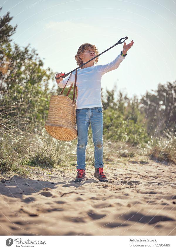 Junge mit Korb, der Müll vom Boden aufhebt. Müllbehälter Kind Container Feld Schulter