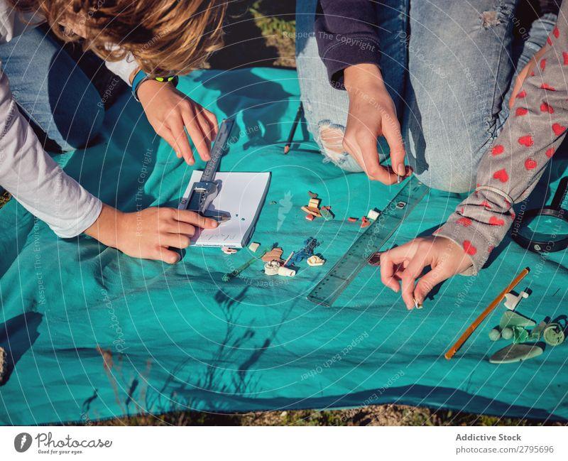 Leute, die kleine Dinge auf Papier auf der Decke messen. Mensch Kunststoff Hand Boden Umwelt