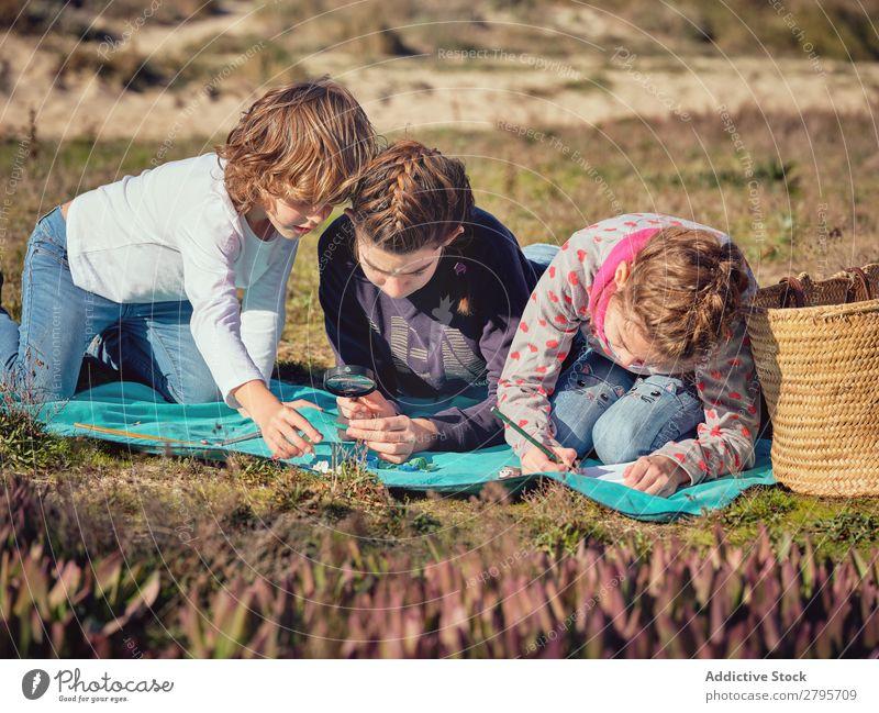 Frau macht Notizen und Kinder messen kleine Dinge auf der Bettdecke. Bleistift Notizbuch Kunststoff Lineal Umwelt