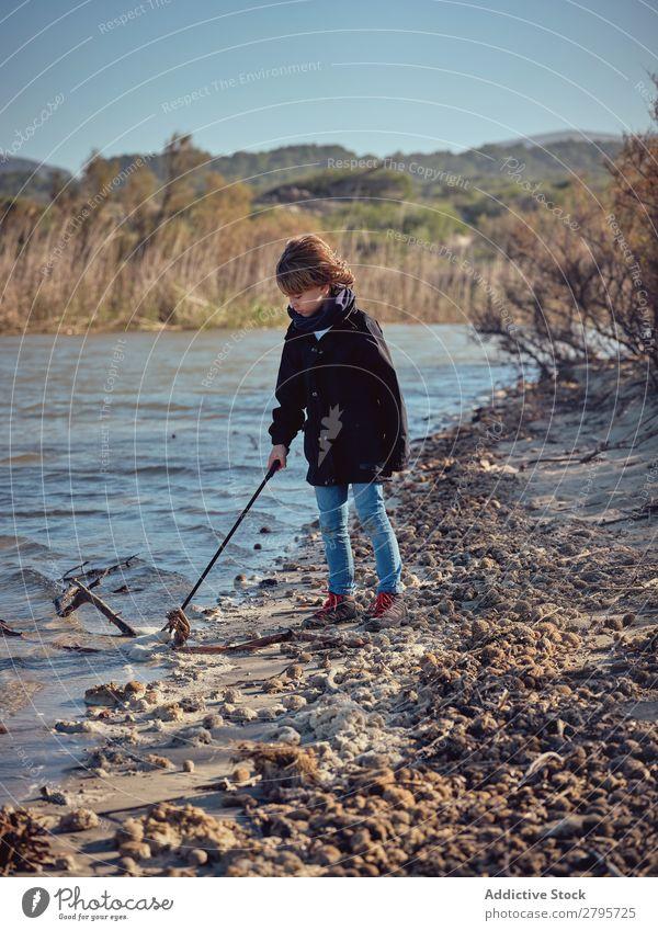 Junge mit Müllabfuhr, der Müll vom Flussufer aufhebt. Müllbehälter Küste Kind Wasser Umwelt