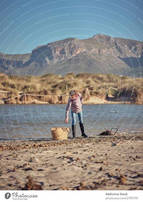 Mädchen in der Nähe des Korbes, das Müll vom Flussufer aufhebt. Müllbehälter Küste Kind Berge u. Gebirge