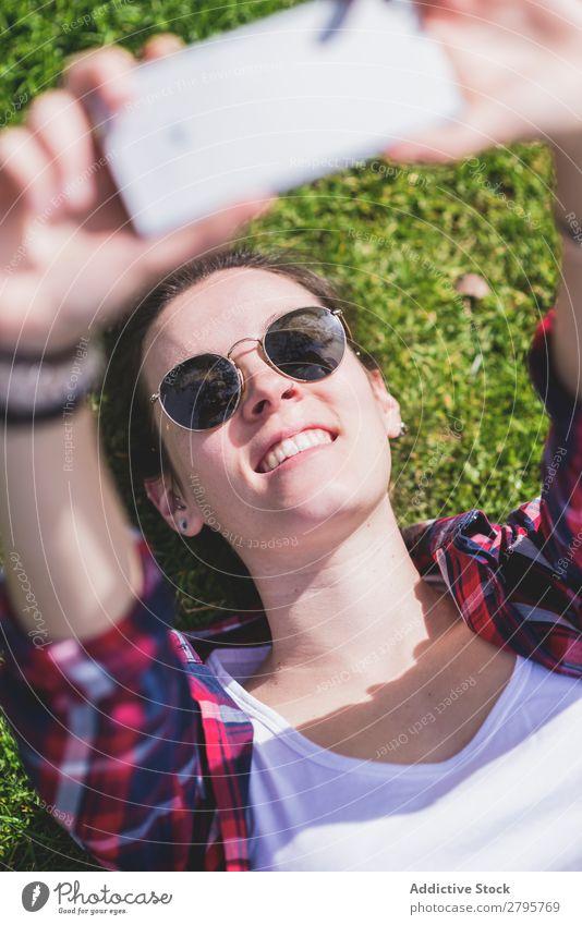 Oben die junge lächelnde Hipsterfrau, die an einem sonnigen Tag im Park auf Gras liegt und dabei mit dem Handy ein Selfie nimmt. obere Ansicht Junge Frau