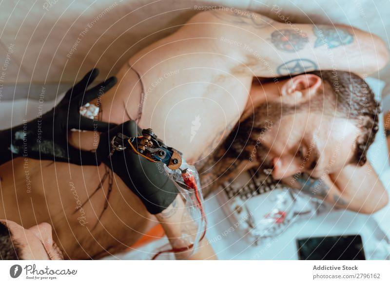 Stilvolle Frau beim Tätowieren Mann Tattoo Künstler Klient Studioaufnahme Werkzeug Zeichnung Piercing Business Arbeit & Erwerbstätigkeit Körper Tinte Mode