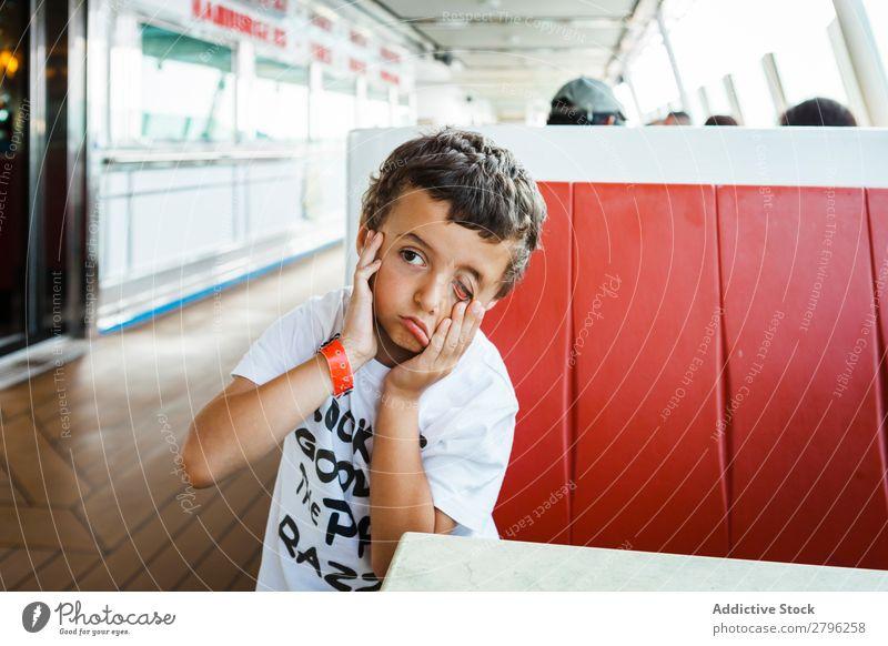 Junge macht Gesicht mit Händen auf dem Sitz konfrontierend Kind lustig Hand sitzen Tisch Grimasse Mann Freude Kindheit Ausdruck Fröhlichkeit Lifestyle