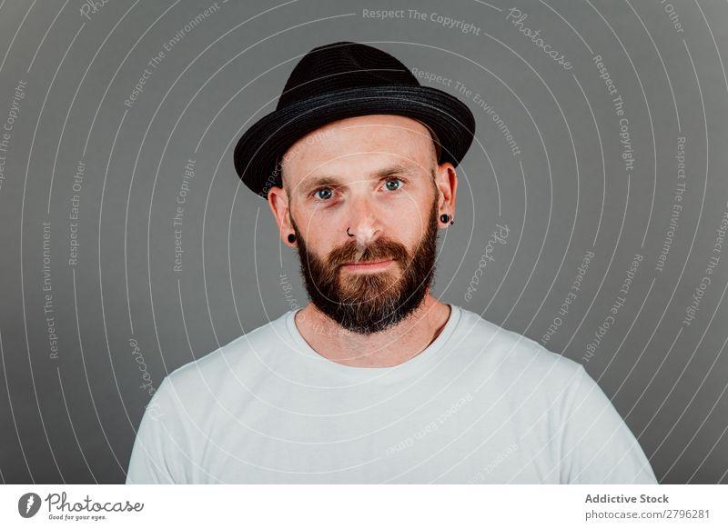 Junger kahlköpfiger Typ mit Hut und schwarzem Hintergrund Mann Schickimicki Glatze Jugendliche bärtig T-Shirt Hand haarlos lässig gutaussehend Coolness Stil
