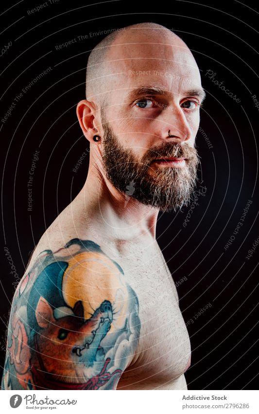 Junger bärtiger Kerl ohne Hemd mit Tattoos Mann Schickimicki Jugendliche Typ Glatze Hand zeigen gutaussehend Kunst Coolness Studioaufnahme Haut Design haarlos